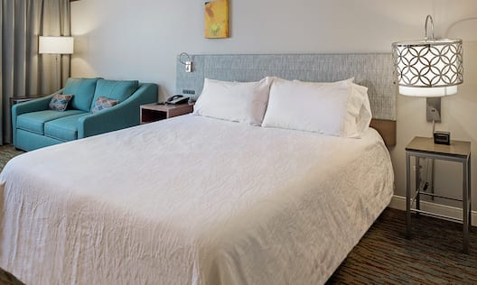 King Bed Between Two Bedside Tables, Illuminated Lamps, and Sleeper Sofa in Standard Guest Room