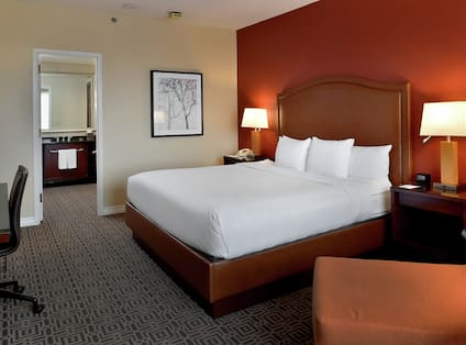 King Presidential Suite with Bed, Work Desk, and Bathroom with Mirror and Vanity