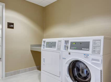 Entry Door, Folding Table, Washer, and Dryer in Laundry Room
