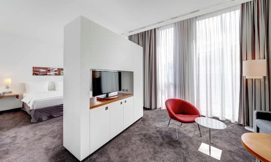 Bed and Living Areas of Junior Suite With TV and Large Window