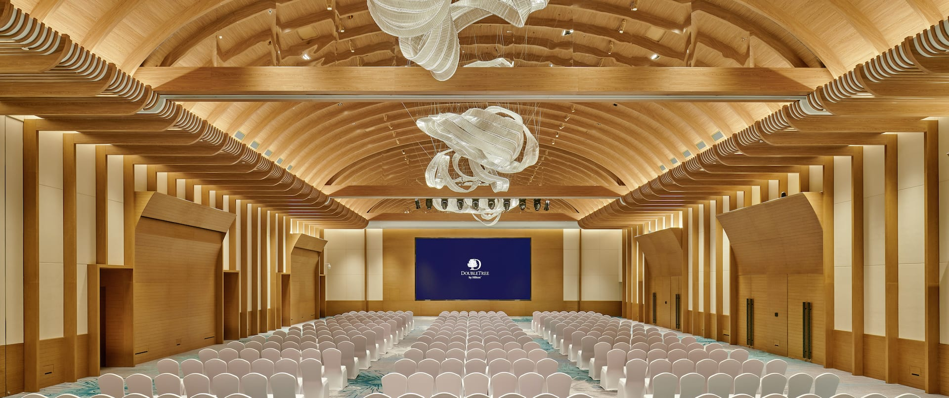 white covered chairs pointed towards a presentation screen in a ballroom