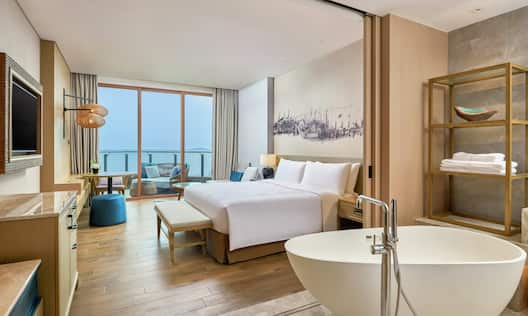 a king bed and a large bathtub in a room with a balcony and view of sea