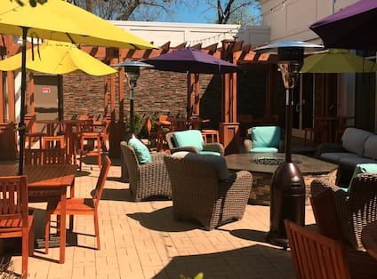 Outdoor Patio Seating Area with Armchairs, Tables and Firepit