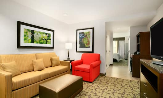 Guest Suite Lounge Area with Sofa, Armchair, Footrest, HDTV and Beverage Station