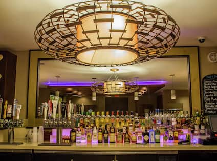 Round Wire Decorated Light Above Refinery Bar with Purple Accent Lights