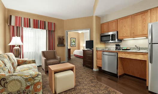 Spacious accessible suite with open concept living area, fully equipped kitchen, and private bedroom.