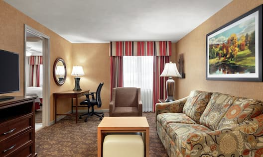 Comfortable living area with sofa, TV, work desk, ergonomic chair, and private bedroom featuring two queen beds.