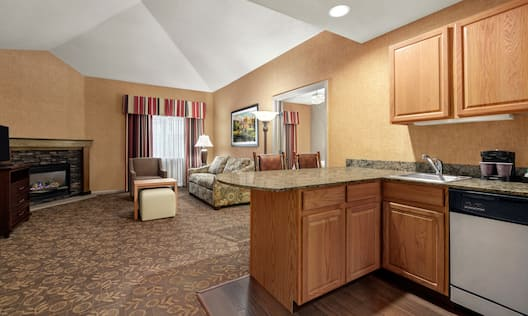 Spacious open concept living area with sofa, fireplace, TV, and kitchen equipped with microwave, fridge, coffee maker, dishwasher, and cook-top stove.