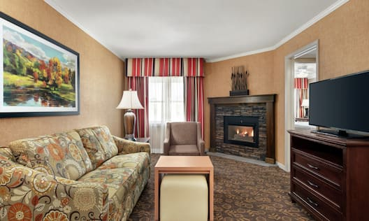Bright in suite living area with beautiful fireplace, sofa, TV, and private bedroom with comfortable king bed.