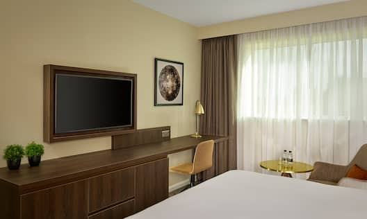 Deluxe guestroom with bed, work desk, and TV