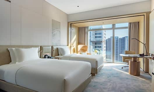 Guest Room with Two Beds Desk and City View
