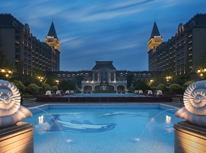 Large outdoor pool lit up at night with grand view of hotel