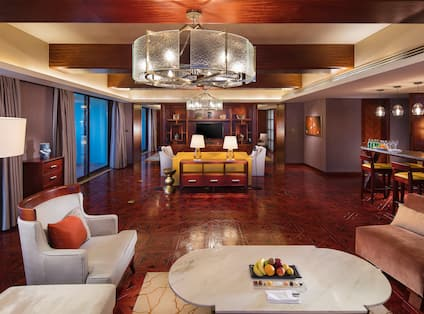 Presidential suite living room with two lounge areas, TV, and partial view of kitchen with bar-style counter top and high chairs