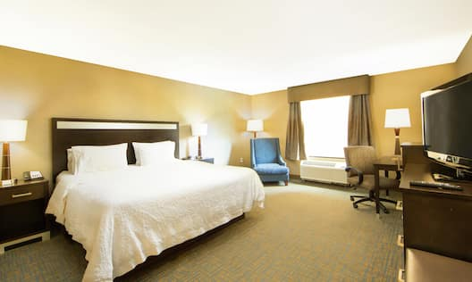 a guest room with a king bed and a blue chair