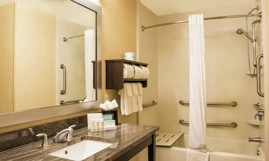 a bathroom with a sink and an accessible tub and shower combo with bench and grab bars