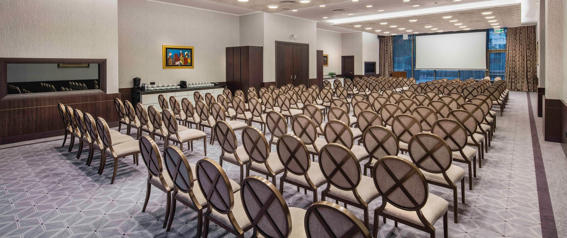 Princess Jelena Meeting Room Arranged Theater Style With Rows of Chairs Facing Projector Screen and Large WIndow