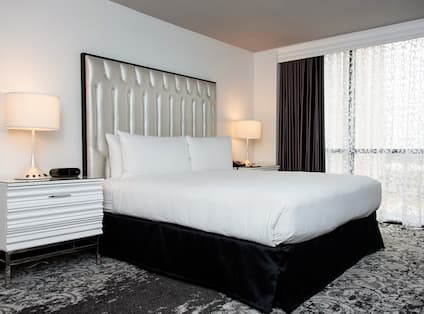 King bed with side table, lamps and large window.