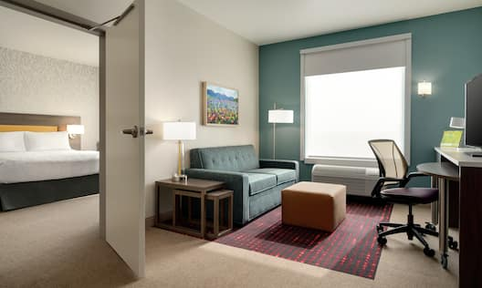 Bright lounge area in suite featuring sofa, TV, work desk, and private bedroom with king size bed.
