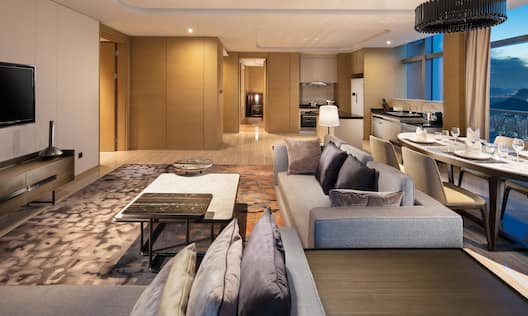Guest Living Room with Sofa, Coffee Table, Wall Mounted HDTV and Dining Table
