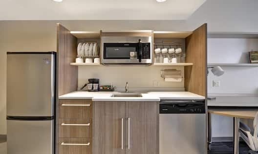 Kitchenette With Full Size Fridge, DIshes and Cups in Cabinets, Coffee Maker, Microwave Over Sink and Dishwasher