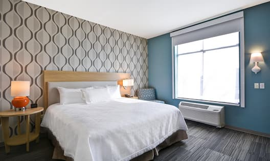 King Bed Between Two Illuminated Lamps and Soft Seating in Corner by Window With Raised Shade