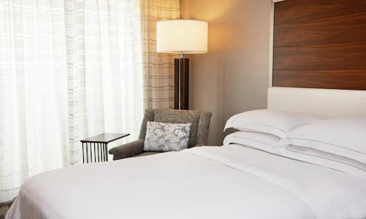 Guest Room with Bed Soft Chair and Small Table