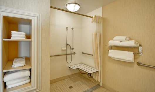 Shelves With Fresh Towels and Roll-In Shower With Shower Seat, Grab Bars, Handheld Showerhead  in Accessible Bathroom