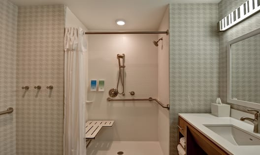 Accessible Guest Bathroom with Roll-In Shower, Bench and Vanity