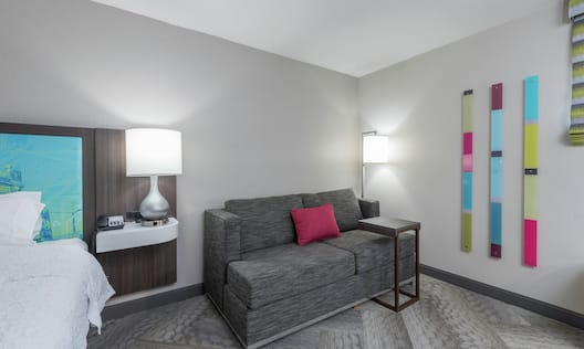Sofa and Table Next to Bed in Guest Room