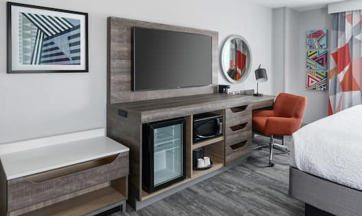 Guest Room with Large Bed Desk HDTV Microwave and Mini refrigerator