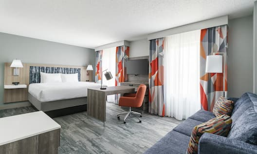 Guestroom with bed, work desk and seating area