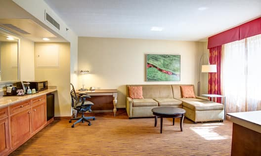 Hospitality Center, Work Desk, Sofa, and Window With Long Drapes in Suite Parlor