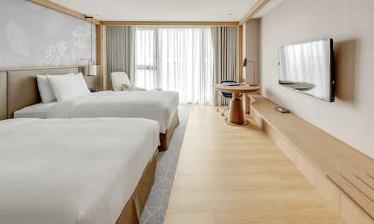 Twin Guestroom with Two Beds, Lounge Area, Work Desk, and Room Technology
