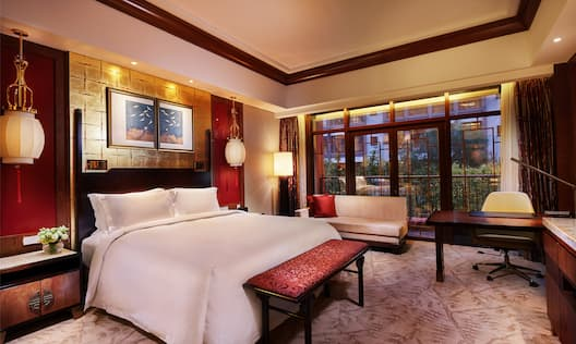 King-Sized Bed, Desk and Love Seat in Deluxe Room