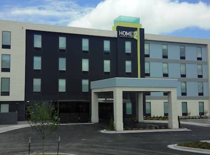 Daytime View of Hotel Exterior WIth Signage, Landscaping, and Porte Cochère