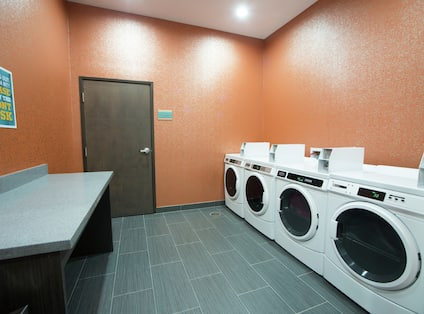 Folding Table, Coin Operated Washing and Drying Machines in Laundry Facility