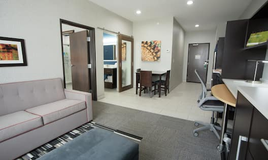 Living Area With Dining Table, Kitchen, Work Desk, and Soft Seating in Studio Suite