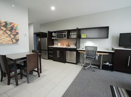 Seating For Three at Dining Table,  Kitchen Area, Work Desk, and TV in Studio Suite