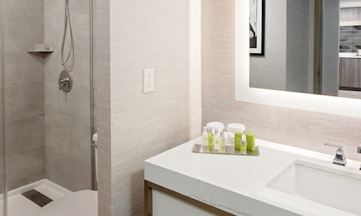 a bathroom vanity with amenities and a walk-in shower