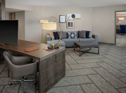 a suite living room and desk with a tv
