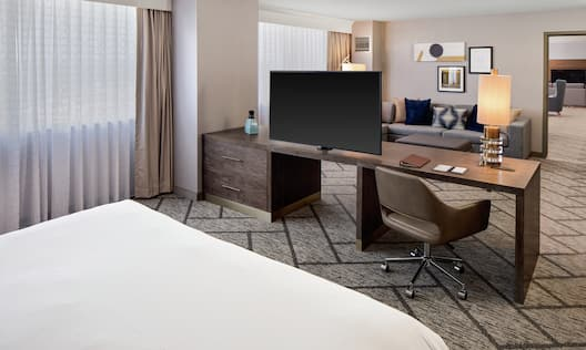 a guest room with a bed, desk, tv and seating area