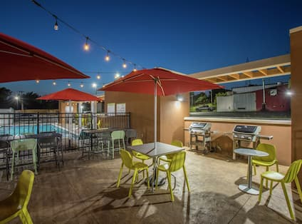 Outdoor Patio Area with Umbrellas, Tables, Chairs and BBQ Grills at Night