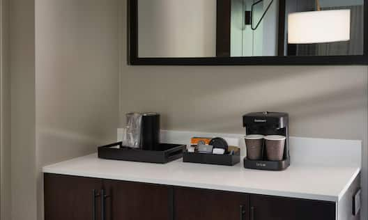 Coffeemaker on credenza with mirror in hotel guest room