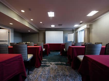 Classroom Setup in Meeting Room With Tables and Chairs Facing Presentation Screen, and Easel