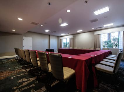 Meeting Room With U-Shaped Table, Chairs, and Windows With Open Drapes
