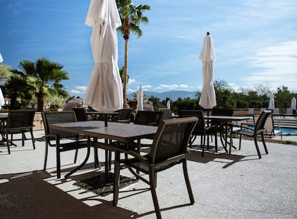 Tables With White Sun Umbrellas and Chairs on Patio