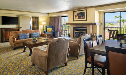 Executive Suite Living Room with TV, Sofa, Chairs, Dining Table, Fireplace, and Outside View