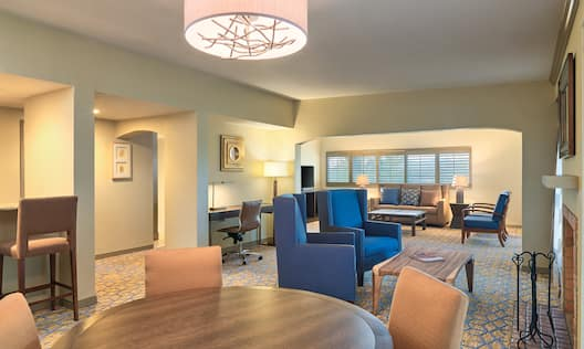 Hospitality Suite Living Area with  Round Table, Chairs, Fireplace, Soft Seating, Sofa and Work Desk