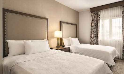 2 beds in room with lamp
