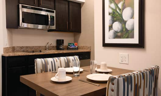 Wall Art Above Dining Table With Seating for Two, Kitchen With Microwave Over Stovetop, Sink, Coffee Maker, and Dishwasher